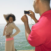 African man talking photograph of African woman next to water — Stock Photo