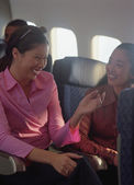 Young women talking on airplane — Stock Photo