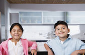 Boy and girl sitting together in kitchen — Stock Photo