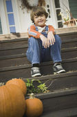 Boy sitting on porch steps smiling next to pumpkins — Stock Photo