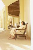 Woman in bathrobe sitting in resort hotel lobby — Stock Photo