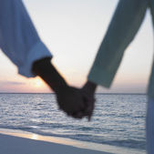 Couple holding hands at the beach — Stock Photo