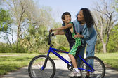 Hispanic mother smiling at son on bicycle — Stockfoto