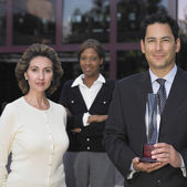 Businesspeople posing for the camera with a glass trophy — Stock Photo