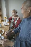 Senior couple sitting at table — Stock Photo