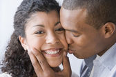 African American man kissing girlfriend on cheek — Stock Photo