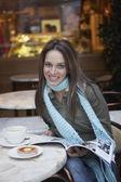 Mujer joven en un café leyendo una revista — Foto de Stock
