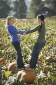 Two girls standing on pumpkin in pumpkin patch — Stok fotoğraf