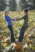 Two girls standing on pumpkin in pumpkin patch — Stock Photo