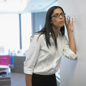 Woman with glass listening through wall in office — Stock Photo
