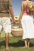 Couple holding a picnic basket — Stock Photo