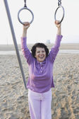 Senior woman holding on to rings at the beach — Stock Photo