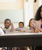 Young students smiling at desks in classroom — Stock Photo