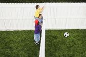 Crianças de raça mista, olhando por cima da cerca na bola de futebol — Foto Stock