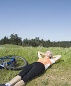 Woman laying in grass next to bicycle — 图库照片