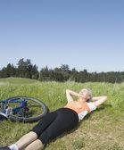 женщина, лежа в траве рядом с велосипедов — Стоковое фото