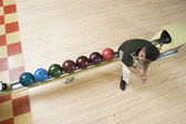 High angle view of man sitting by bowling balls — Стоковое фото