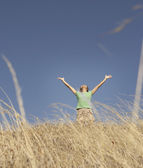 Woman standing with her arms outstretched — Stock Photo