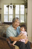 Asian grandfather holding young granddaughter on lap — Stock Photo