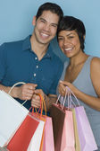 Hispanic couple holding shopping bags — Stock Photo