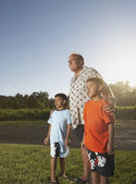 Father and sons standing together on green lawn — Stock Photo