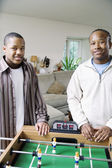 Two males behind foosball table — Stock Photo