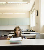 Boy sitting at desk in empty classroom — Stock Photo