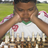 African boy looking at chess board outdoors — Stock Photo