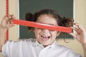目の上のヒスパニック系の女の子ホールディング定規 — ストック写真