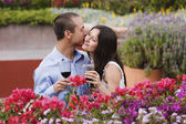Hispanic couple kissing with wine — Stock Photo
