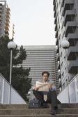 Businessman reading newspaper on steps — Stock Photo
