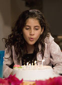 Hispanic girl blowing out birthday candles — Stock Photo