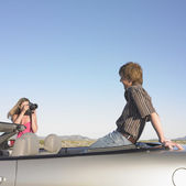 Woman taking picture of man sitting in convertible — Stock Photo