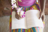 Low section of woman sitting in chair reading book while holding flowers — Stok fotoğraf