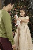 Hispanic father watching daughter open Christmas gift — Stock fotografie
