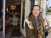 Middle-aged woman standing in front of antique shop — Stock Photo