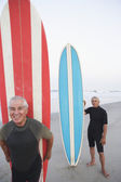 Senior surfers holding their boards at the beach — Stock Photo