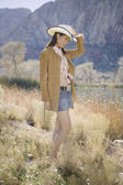 Young woman in cowboy outfit posing for the camera — Stock Photo