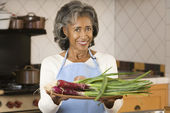 Senior African woman holding plate of vegetables — Stock Photo