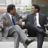 Two businessmen talking on outdoor bench — Stock Photo