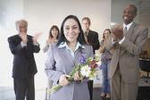 Affärskvinna hålla blommor medan medarbetare applåderar — Stockfoto