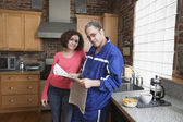 Couple in kitchen reading newspaper — Stock Photo