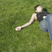 Asian woman listening to mp3 player in grass — Stock Photo