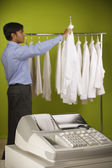 Man looking at shirt off rack next to cash register — Stock Photo