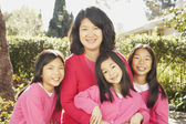 Asian mother with three young daughters smiling outdoors — Stock Photo