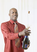 African man popping cork on champagne — Stock Photo