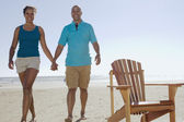 Portrait of couple holding hands and walking on beach — Stock Photo