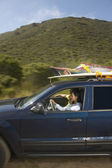 Couple driving SUV on road trip — Stock Photo