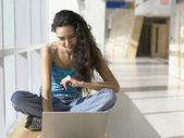 Portrait of young woman with laptop in hallway — Stock Photo