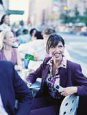 Businesswoman at outdoor restaurant laughing — Stockfoto